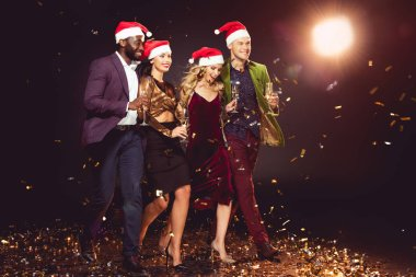 glamorous multiethnic friends in santa hats holding champagne glasses and walking on confetti with backlit