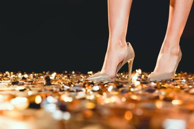 Partial view of woman in high heel shoes standing on golden confetti stock vector