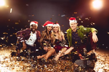 happy multicultural friends in santa hats holding champagne glasses and sitting on confetti