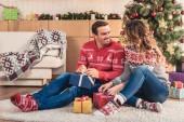 manžel a manželka vánoční dárky a díval se na sebe doma