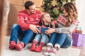 Fotografie parents gifting christmas present to daughter at home