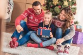 Fotografie adorable daughter holding gift box near christmas tree at home