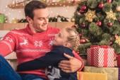 Vater umarmt Tochter in der Nähe von Weihnachtsbaum zu Hause und sie sahen einander