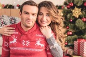 smiling wife hugging husband and looking at camera at home, christmas tree on background