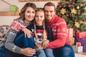 smiling parents and daughter hugging and sitting near christmas tree and presents at home