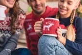 Photo selective focus of parents and daughter with christmas cups of cappuccino at home