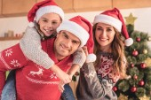 father in santa hat giving piggyback to daughter and looking at camera at home