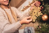 cropped image of preteen kid decorating christmas tree with golden snowflake at home