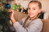 Fotografie adorable preteen kid decorating christmas tree at home and looking at camera