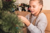 adorable preteen kid decorating christmas tree at home