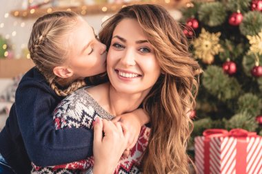 adorable daughter kissing smiling mother near christmas tree at home