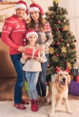 family in santa hats with dog in deer horns standing near christmas tree with gifts