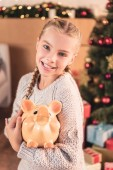 rozkošný usmívající se dítě drží prasátko doma s vánoční stromeček