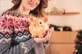 oříznutý pohled na ženu ve vánoční svetr drží velké prasátko