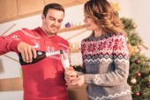 happy couple in christmas sweaters, smiling husband pouring champagne for wife