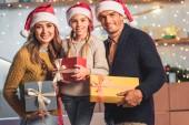 Fényképek boldog család santa kalap tartja karácsonyi ajándék doboz otthon