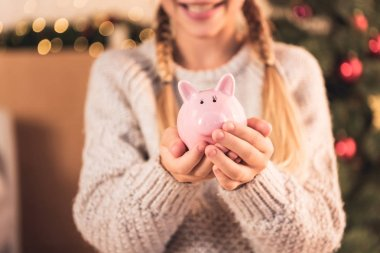 cropped view of female youngster holding pink piggy bank