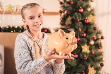 smiling preteen kid holding big piggy bank at home with christmas tree