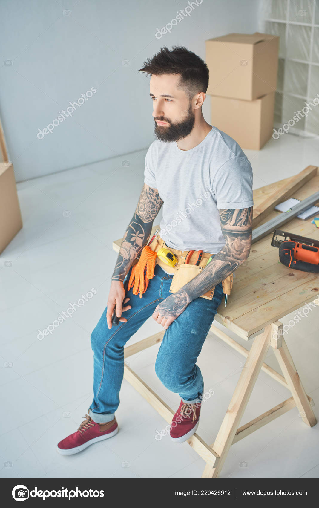 720def32c High angle view of bearded repairman with tattoos and tools leaning on  wooden surface in new apartment — Photo by ...