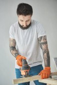 Fotografia handsome bearded tattooed man holding wooden plank and using electric jigsaw
