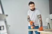 pohledný vousatý Tetovaný muž pomocí elektrické skládačky a při pohledu na fotoaparát
