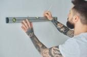 Fotografia ritagliata colpo di giovane che tiene il livello strumento e marcatura muro con la matita durante le riparazioni