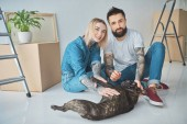 Photo happy young couple playing with french bulldog and smiling at camera in new home