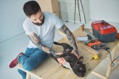 Photo tattooed man playing with french bulldog on wooden surface in new apartment