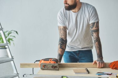 cropped shot of bearded man leaning at wooden table with electric jigsaw during home repair