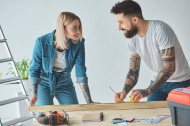 young tattooed couple smiling each other while holding pencil, wooden plank and measuring tape