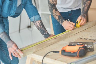 cropped shot of tattooed couple working with wooden plank and measuring tape