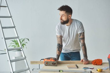 handsome bearded man leaning at wooden table and looking away during house repair