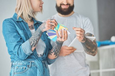 cropped shot of happy young couple choosing colors for house repair