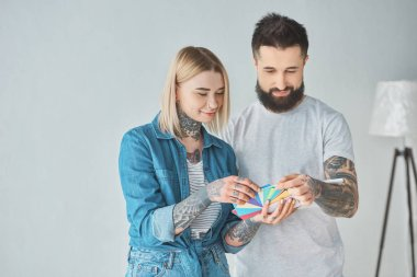 smiling young tattooed couple choosing colors for house repair