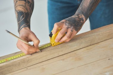 cropped shot of man holding pencil and measuring tape while working with wooden planks