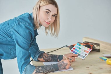 young tattooed woman holding color palette and smiling at camera during home improvement