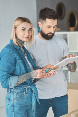 young tattooed couple using digital tablet together in new house