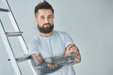 handsome bearded tattooed young man standing with crossed arms near stepladder and looking at camera on grey