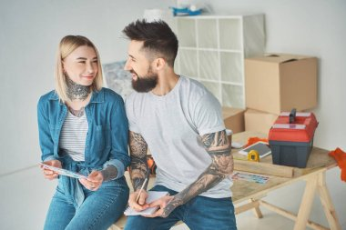 happy young couple holding color palette and notebook in new house