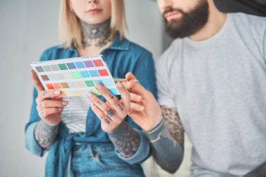 cropped shot of young tattooed couple holding palette of colors and choosing color for home improvement