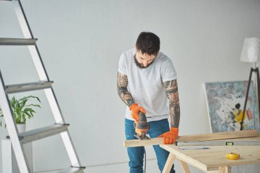 handsome bearded tattooed man using electric jigsaw during house repair