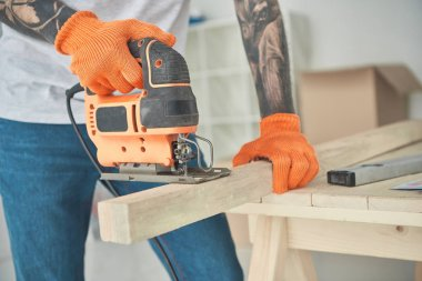 close-up partial view of of young tattooed man using electric jigsaw
