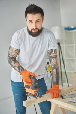 handsome bearded man using electric jigsaw and looking at camera