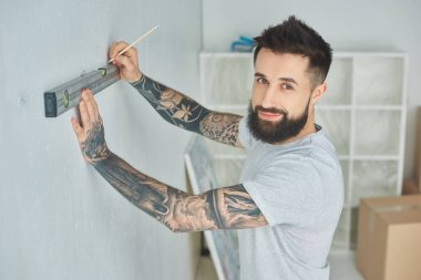 handsome bearded young man holding level tool and smiling at camera during home improvement