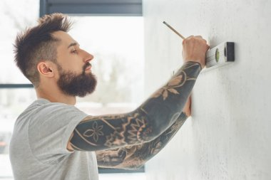 side view of bearded young man holding level tool and marking wall with pencil during repairs
