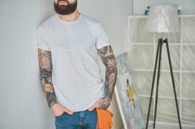cropped shot of bearded tattooed man leaning at wall in new house