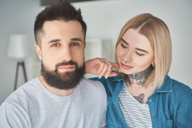 portrait of beautiful happy young couple with tattoos in new home