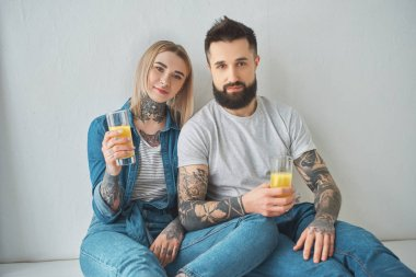 young tattooed couple holding glasses of juice and looking at camera while sitting in floor in new house
