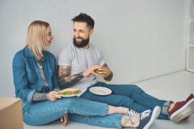 happy young couple holding sandwiches and smiling each other in new house