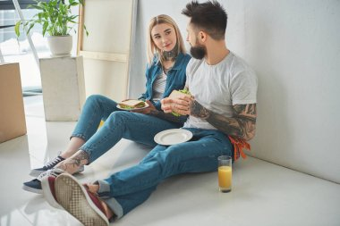 Young tattooed couple eating sandwiches and looking at each other while sitting on floor i new house stock vector